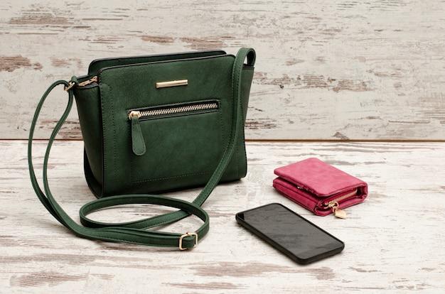 Pequena bolsa feminina verde, bolsa e telefone em um de madeira
