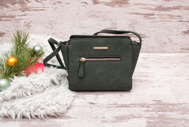 Pequena bolsa feminina verde em uma superfície de madeira, galho de abeto com enfeites