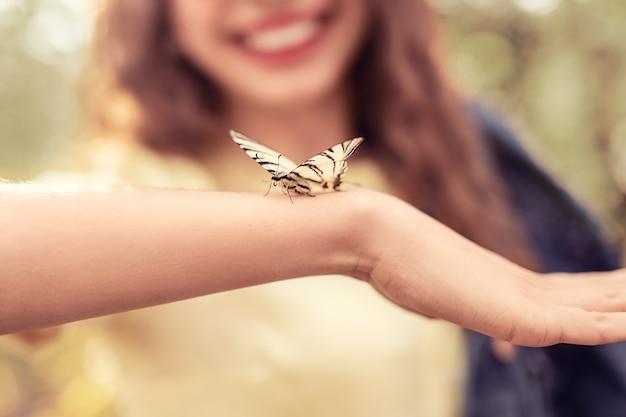 Pequena borboleta com asas listradas sentada no braço de uma senhora desfocada em um dia calmo de verão