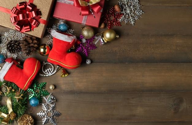 Pequena bota de papai noel com decorações e caixas de presente com fundo de madeira