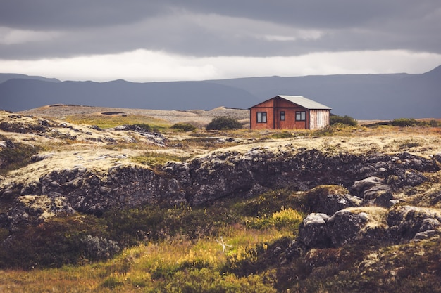 Pequena cabana de madeira na paisagem vulcânica da islândia