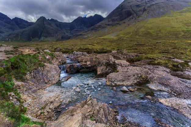 Pequena cachoeira e riacho ao longo da rota de caminhada de the fairy pools em glen brittle, na ilha de skye, na escócia