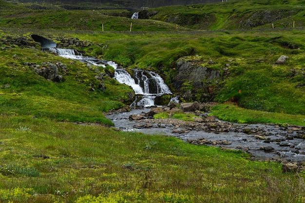Pequena cachoeira em uma curva no anel viário na islândia