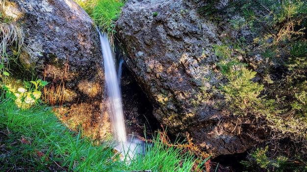 Pequena cachoeira entre rochas na montanha com plantas verdes e longa exposição.