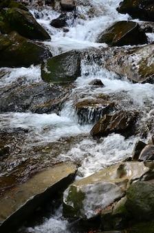 Pequena cachoeira selvagem sob a forma de pequenos riachos de água entre as pedras da montanha