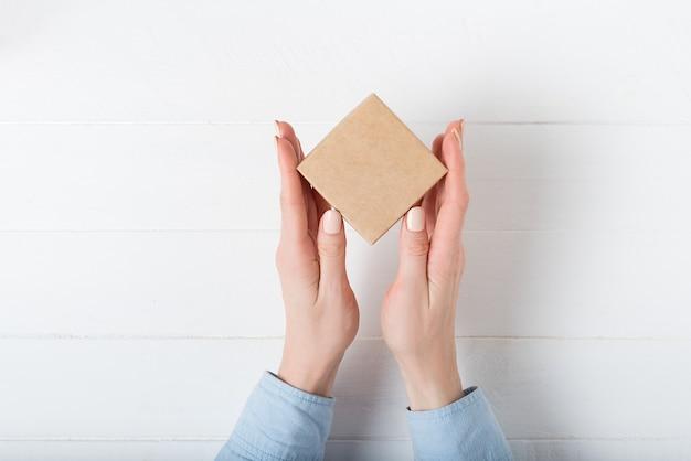 Pequena caixa de papelão quadrada nas mãos femininas.
