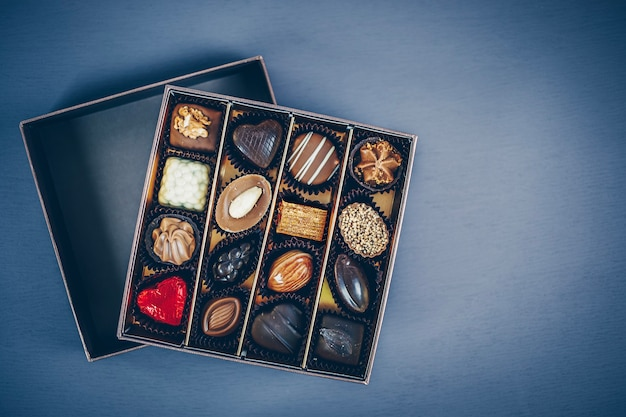 Pequena caixa quadrada de bombons de chocolate e trufas de diversos formatos e recheios