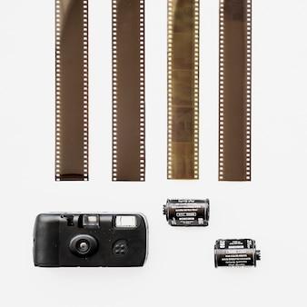 Pequena câmera retro perto de filmstrips