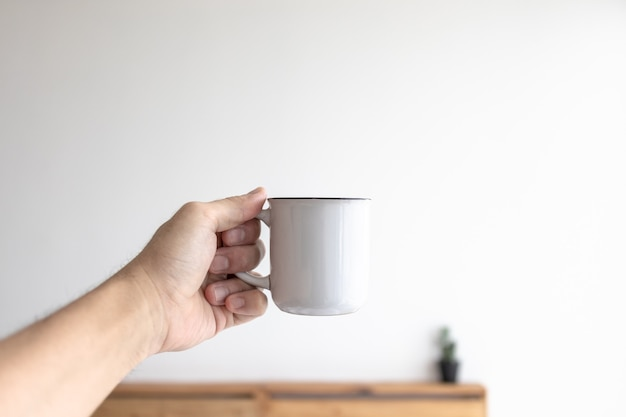 Pequena caneca branca de café em uma sala branca e aconchegante pela manhã.