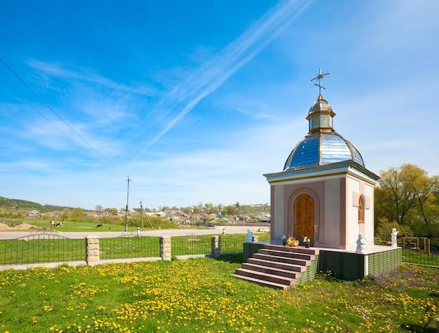Pequena capela rural na clareira de flores da primavera