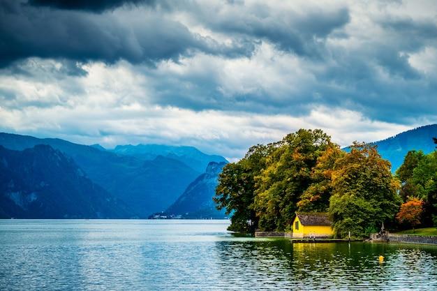 Pequena casa amarela perto da floresta no amplo lago traunsee em gmunden