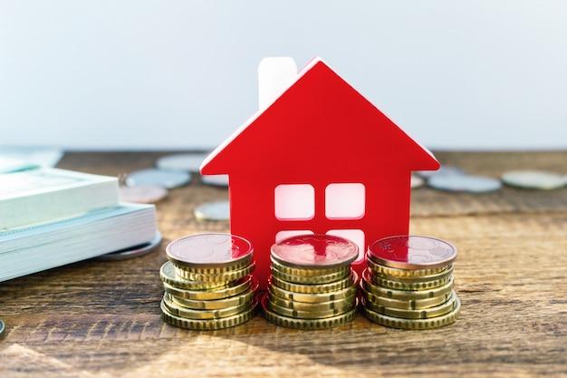 Pequena casa ao lado de moedas empilhadas