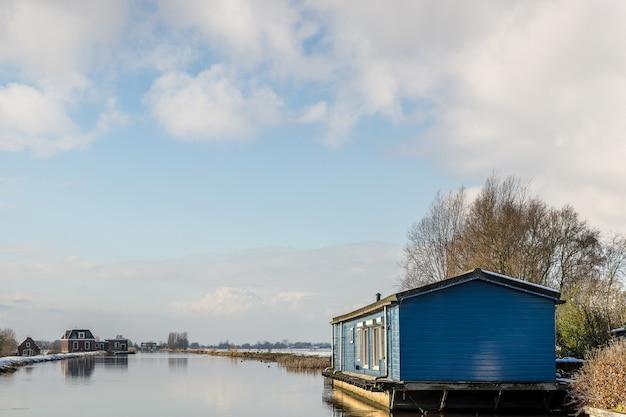 Pequena casa azul sobre a água com edifícios à distância sob um céu azul