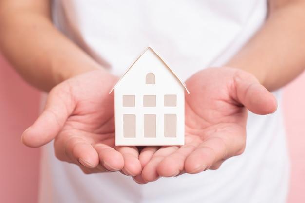 Pequena casa branca na mão humana