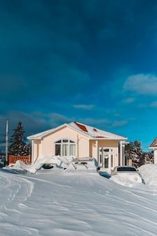 Pequena casa com carros na frente cobertos de neve