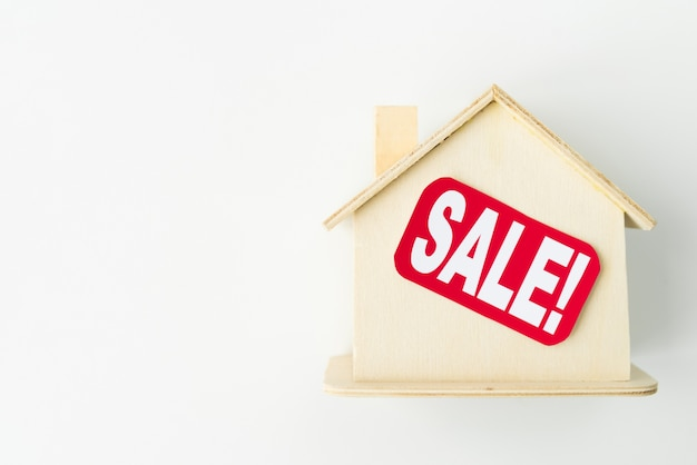 Pequena casa de madeira com sinal de venda