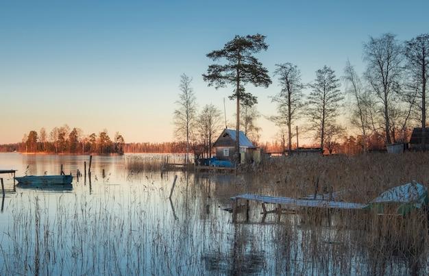 Pequena casa de madeira de pesca com um cais e barcos na margem do lago norte no início da primavera em um dia ensolarado.