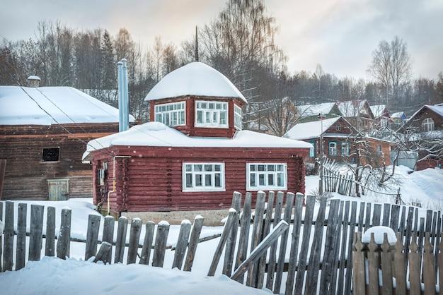 Pequena casa de madeira e uma cerca em plyos à luz de um dia de inverno sob um céu azul