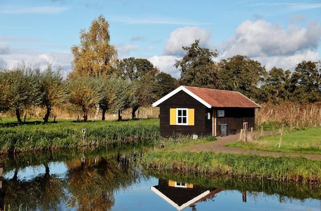 Pequena casa de madeira perto do lago em uma área rural