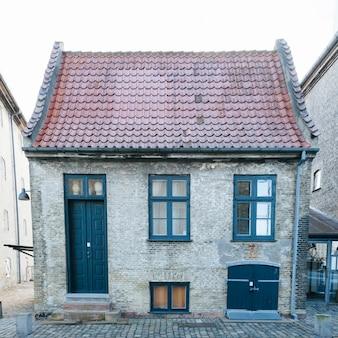 Pequena casa de tijolos com telhado de azulejos