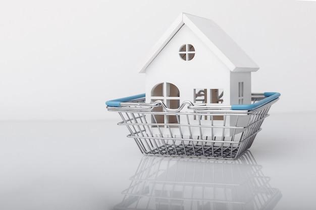 Pequena casa decorativa de madeira em um conceito de compra ou venda de carrinho de compras