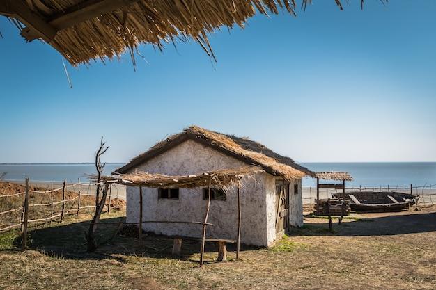Pequena casa velha, poço de madeira e um barco furado à beira-mar