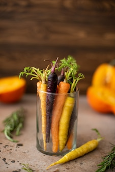 Pequena cenoura multicolorida em um copo sobre uma mesa de madeira
