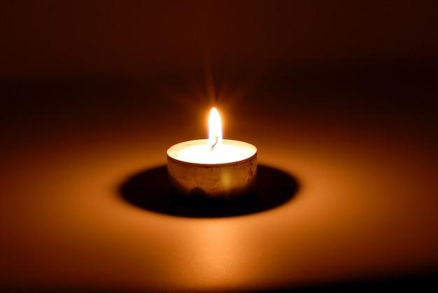 Pequena chama de uma vela acesa na escuridão
