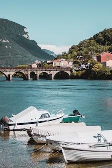 Pequena cidade com ponte cais e barcos na costa do lago de como, na paisagem montanhosa da itália