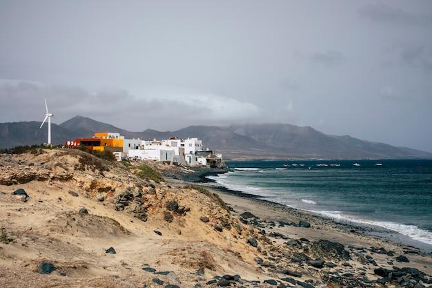 Pequena cidade na costa perto das ondas do oceano com pequenas casas e caravanas