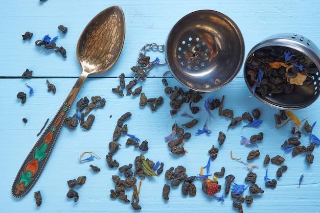 Pequena colher de chá decorativa com folhas de chá e filtro