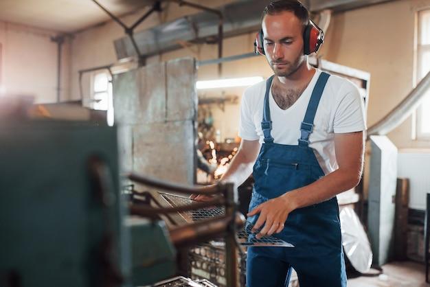 Pequena construção de metal. homem de uniforme trabalha na produção. tecnologia industrial moderna.