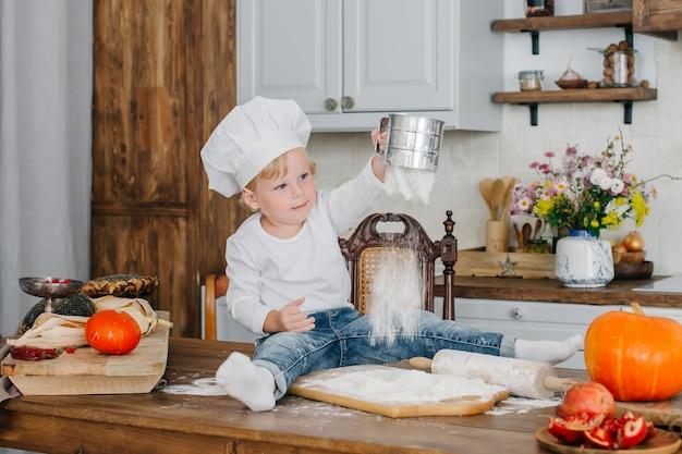 Pequena cozinheira está cozinhando na cozinha. ficamos em casa, brincamos com farinha e cozinhamos com nossos filhinhos.