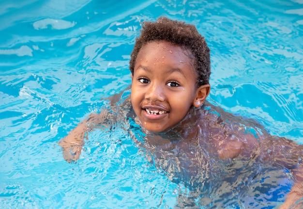 Pequena criança africana espirrando na piscina