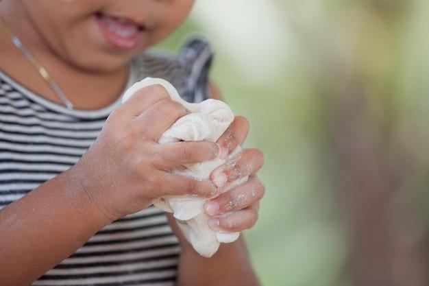 Pequena criança com mãos amassando massa