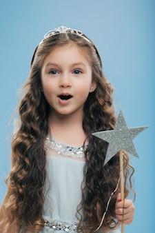 Pequena criança criança princesa usa coroa e vestido, segura a varinha mágica