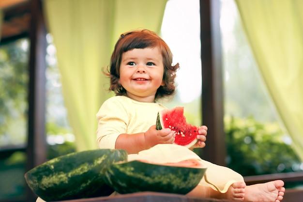 Pequena criança encaracolada come uma melancia suculenta no jardim. as crianças comem frutas na rua. comida saudável para as crianças. jardinagem da criança.
