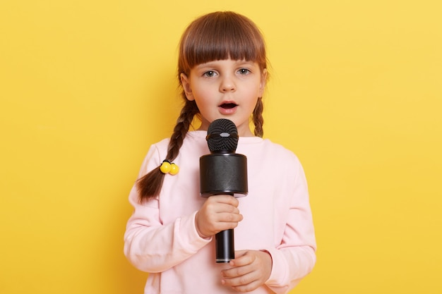 Pequena criança europeia do sexo feminino canta no microfone, parece concentrada, quer ser uma ótima cantora, pequena e linda artista organiza show, vestindo um suéter rosa claro.