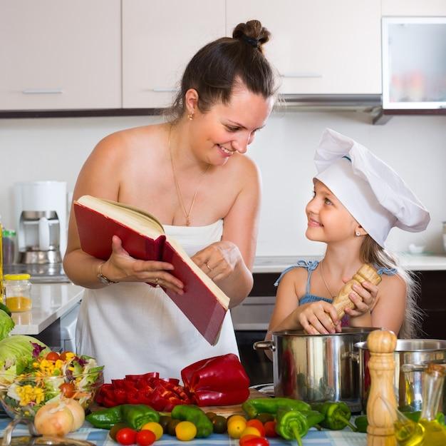 Pequena e mãe com livro de culinária