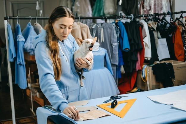 Pequena empresa, estilista, alfaiate, local de trabalho de costureira. sincero retrato do estilista criando a roupa, alfaiate costura vestido na mesa.