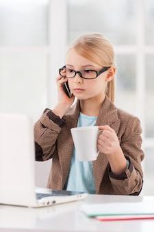 Pequena empresária. menina confiante de óculos e trajes formais falando ao telefone enquanto está sentada à mesa e olhando para o laptop