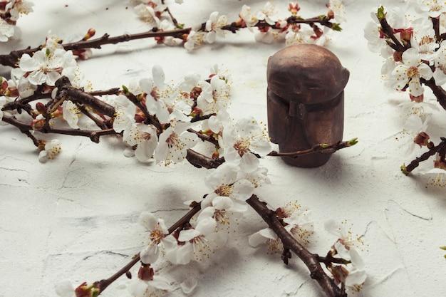 Pequena estatueta monge budista e um raminho de flores de cerejeira em uma superfície de pedra clara. conceito das férias de primavera e ano novo para o calendário asiático