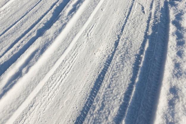 Pequena estrada no inverno com sulcos de pneus de carros. no terreno há neve após queda de neve.