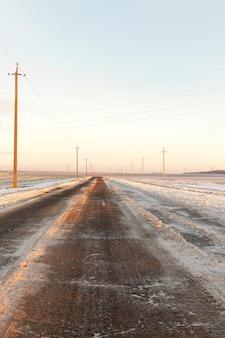 Pequena estrada rural coberta de neve no inverno. foto close-up ao pôr do sol. céu colorido ao fundo