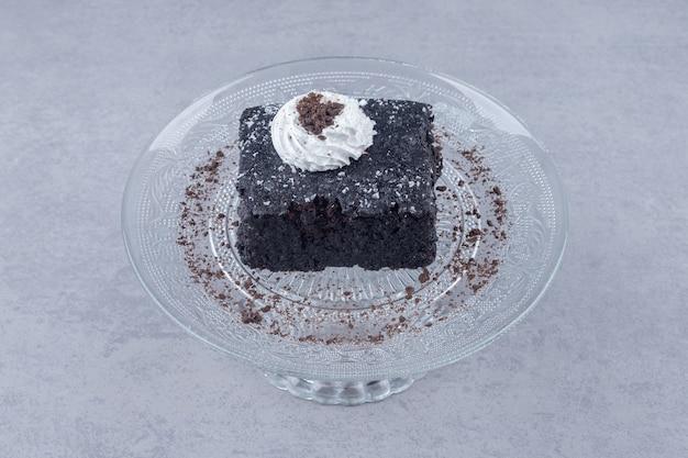 Pequena fatia de bolo de chocolate em uma travessa de vidro sobre mármore