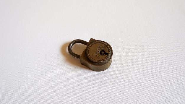 Pequena fechadura metálica colocada sobre uma superfície branca