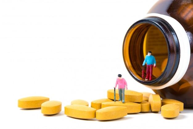 Pequena figura velho ou paciente segurando a bengala com pílula de vitamina c ou comprimidos