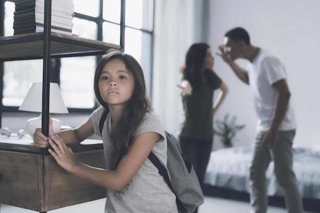Pequena garota de cabelos escuros e pais que discutem atrás dela