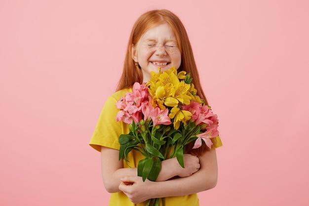 Pequena garota ruiva de sardas com duas caudas, com os olhos fechados amplamente sorrindo e parece fofa, segura o buquê, usa uma camiseta amarela, fica sobre fundo rosa.
