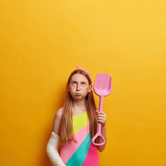 Pequena garota sombria com longos cabelos ruivos, assoa as bochechas e olha para cima, brinca na areia da praia com uma pá, faz castelo de areia, vestida de maiô, feriu o braço engessado, espaço vazio acima